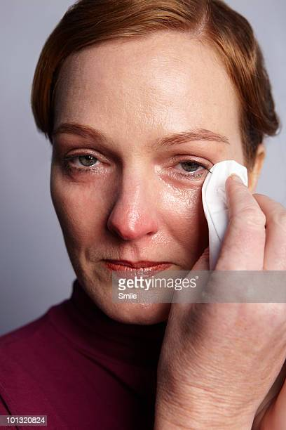Sad woman wiping her eyes