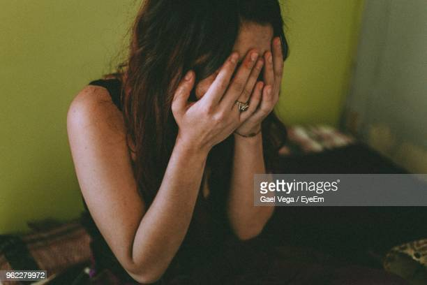 sad woman with hands covering face sitting at home - kopf in den händen stock-fotos und bilder