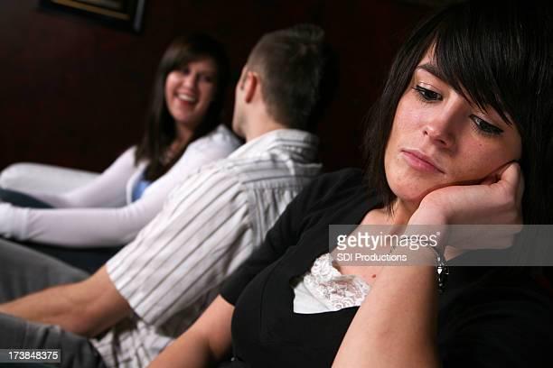 Triste donna con coppia felice dietro sua