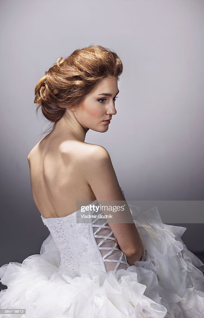 Sad Young Bride In Wedding Dress Standing Against Gray Background ...