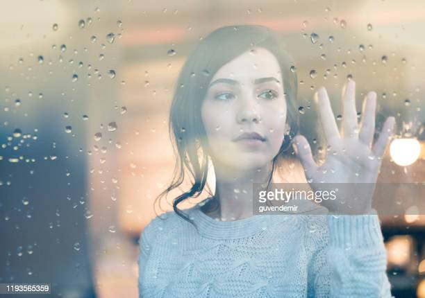 sad young cute woman looking through window on rainy day - mourning stock pictures, royalty-free photos & images