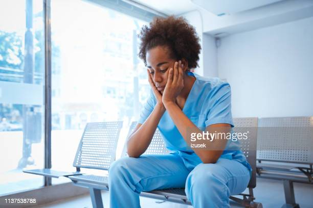 sad young female nurse sitting with hands on chin - despair stock pictures, royalty-free photos & images