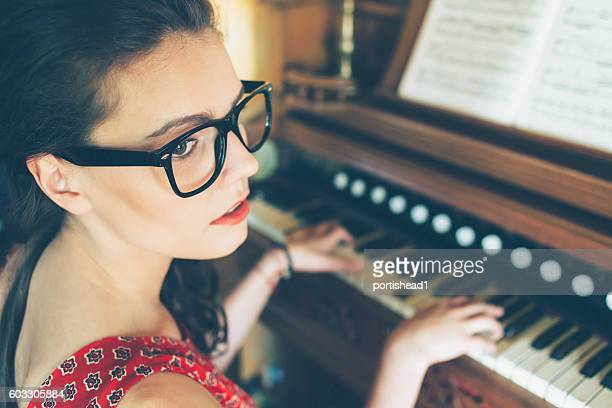 Sad young female pianist practicing at home