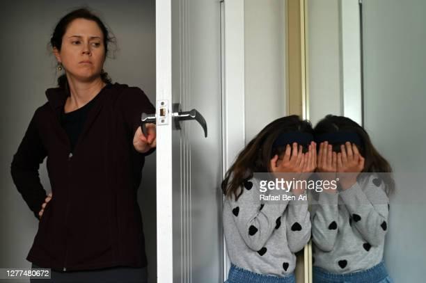 sad young girl covering her face hiding from mother - rafael ben ari stock-fotos und bilder