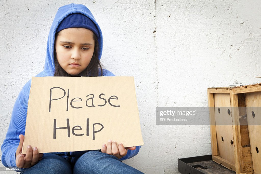 Sad young girl holding Please Help sign : Stock Photo