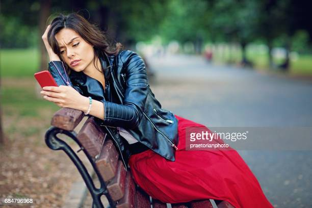 Sad young girl is getting bad news on her mobile phone