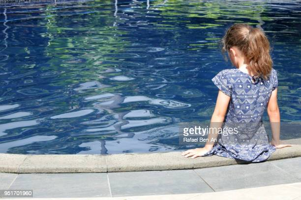 Sad young girl sits on a poolside