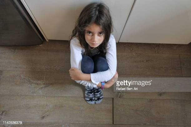 sad young girl sitting alone looking at camera - rafael ben ari fotografías e imágenes de stock