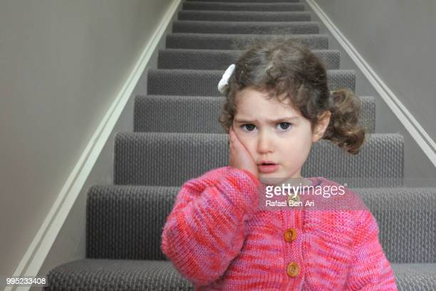 sad young girl sitting on staircase at home - rafael ben ari stock pictures, royalty-free photos & images