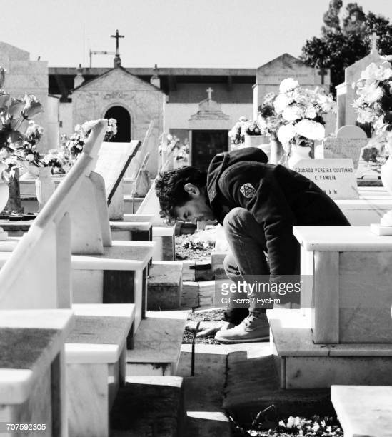 Sad Young Man Sitting Amidst Tombstones In Cemetery