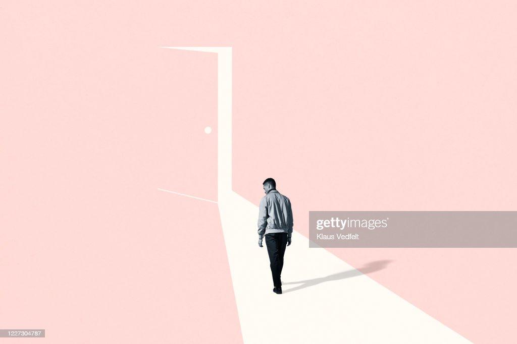Sad young man walking towards ajar door : Stock Photo