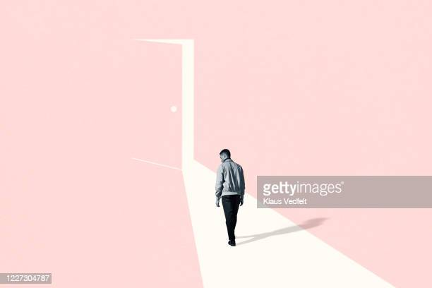 sad young man walking towards ajar door - hope stock pictures, royalty-free photos & images