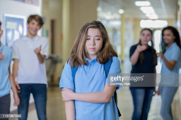 sad young teenage girl walks in school hallway while bullies tease her - teenagers only stock pictures, royalty-free photos & images