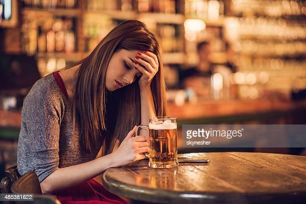 Traurige Junge Frau mit einem Kopfschmerz und Sitzbereich in der bar.