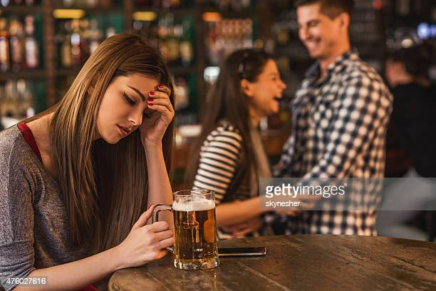 Sad young woman in bar with happy couple in background.