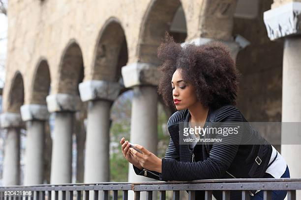 Sad young woman in front of ancient columns
