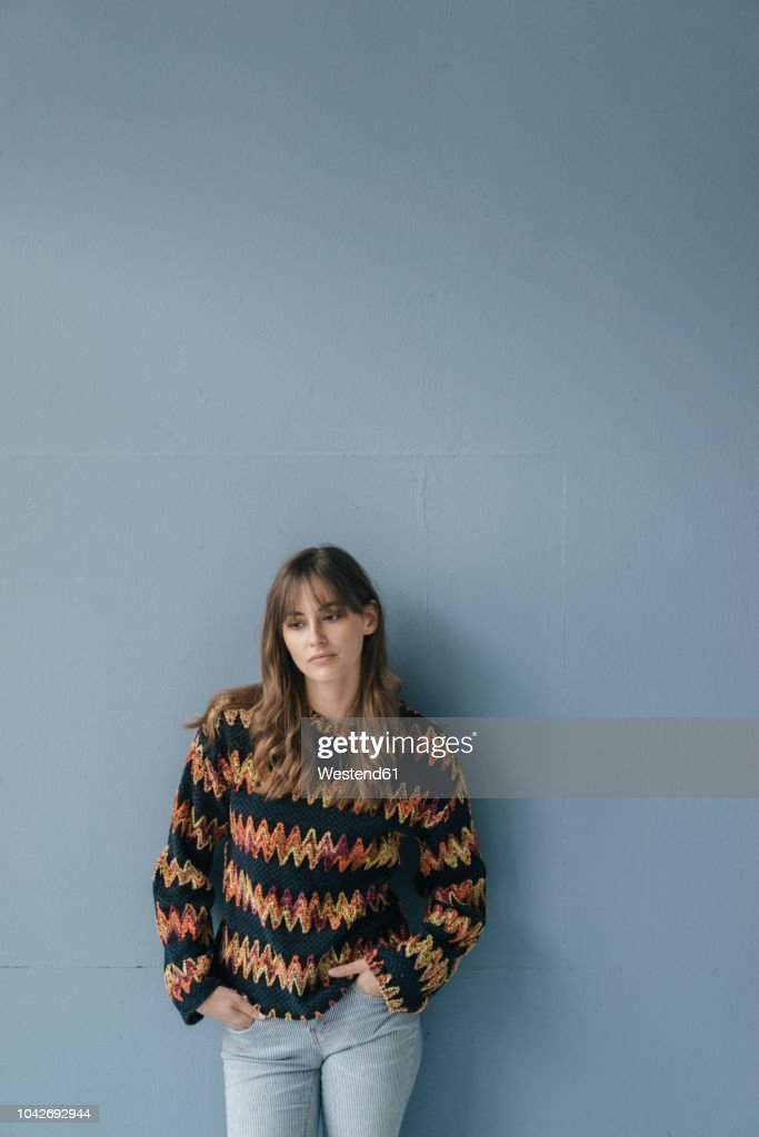 Sad young woman leaning against wall, with hands in pockets : Stock Photo