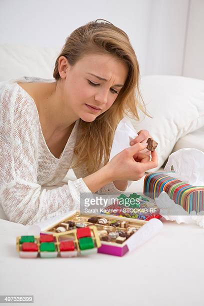 Sad young woman on couch nibbling sweets