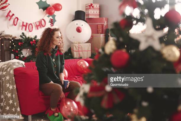 sad young woman sitting alone on sofa at christmas - solitude stock pictures, royalty-free photos & images