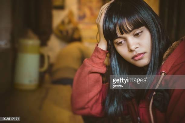 sad young woman sitting in kitchen. - capelli neri foto e immagini stock