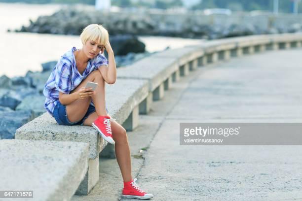 Sad young woman sitting on beach