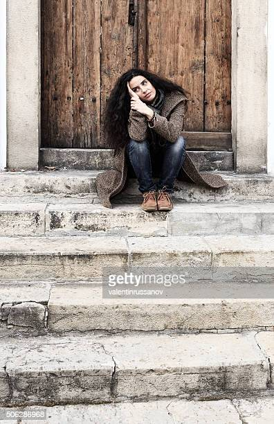 Sad young woman sitting on stairs at the door