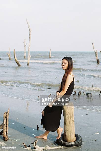 sad young woman sitting on wooden post at beach against clear sky - my lai sit fotografías e imágenes de stock