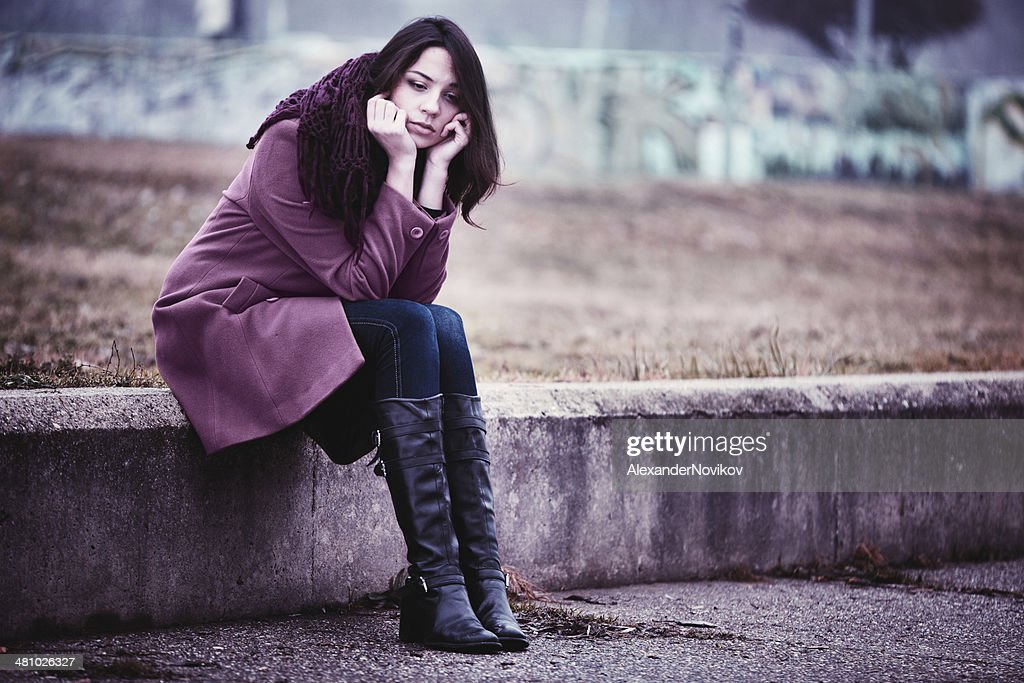 Sad Young Woman Sitting Outdoors : Stock Photo