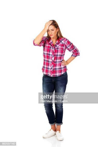 sad young woman standing against white background - kopf in den händen stock-fotos und bilder