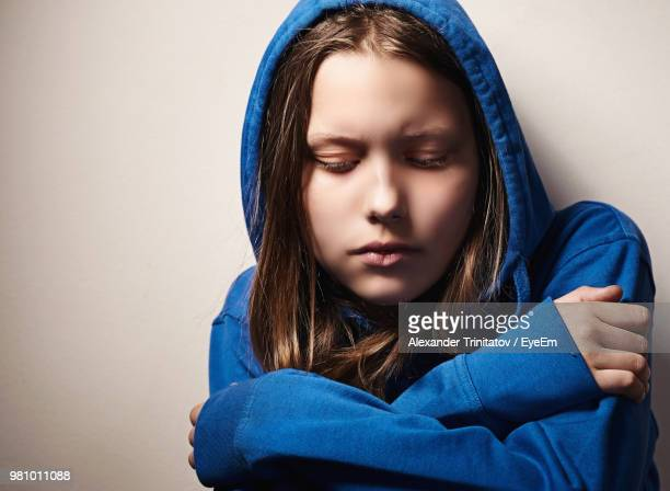 Sad Young Woman Wearing Hooded Shirt Against White Background