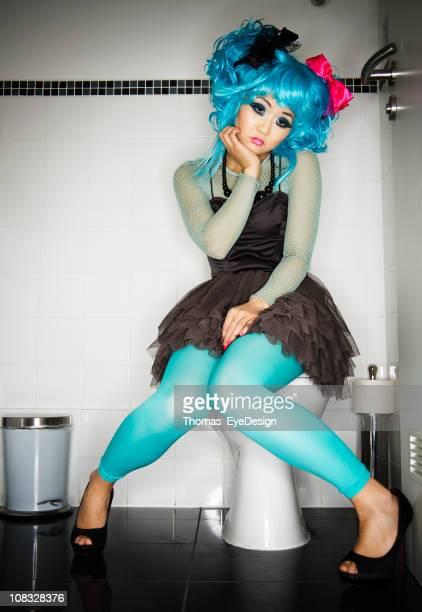 Triste jeune femme portant Manga vêtements assis dans la salle de bains