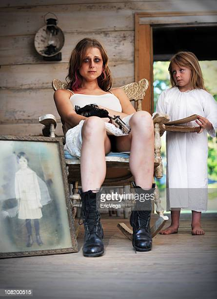 sad young woman with gun beside little angel girl - young goth girls stock pictures, royalty-free photos & images