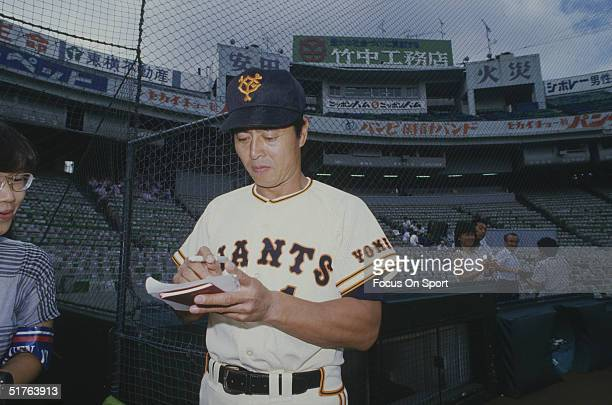 Sadaharu Oh of the Yomiuri Giants autographs a sheet of paper for a fan during a game in Tokyo Japan circa 1990's