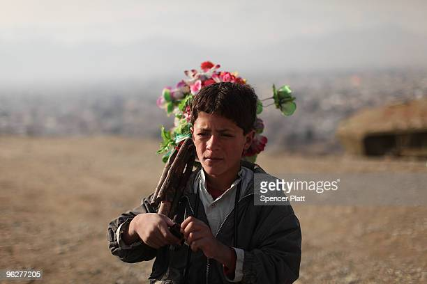 Sadam sells flowers and takes peoples' pictures which he then sells them on a hillside overlooking Kabul on January 30 2010 in Kabul Afghanistan...