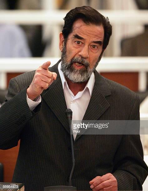 Saddam Hussein defiantly speaks to the Presiding Judge Rizgur Ameen Hana AlSaedi as his trial begins held under tight security in Baghdad's heavily...
