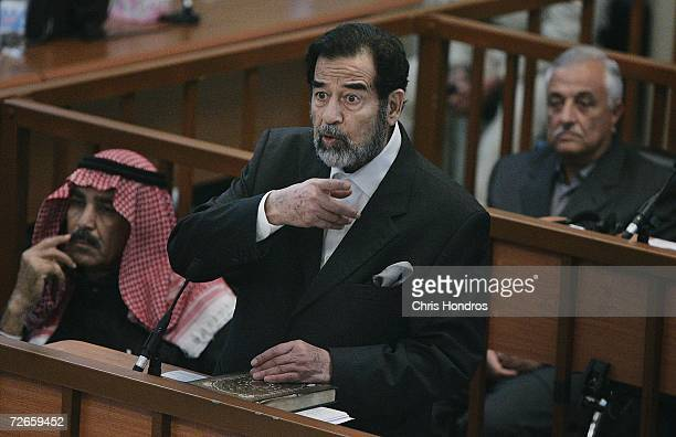 Saddam Hussein flanked by codefendants Farhan Salah and Sabir alDouri speaks in court during the continuation of his 'Anfal' genocide trial November...