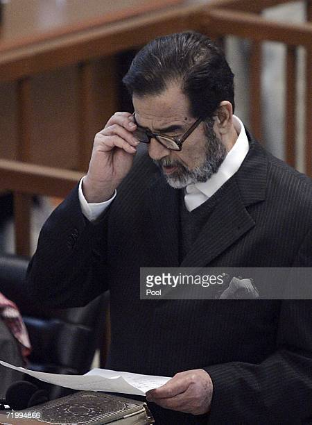 Saddam Hussein reads a document during his genocide trial inside the fortified Green Zone on September 26 2006 in Baghdad Iraq Saddam and seven...