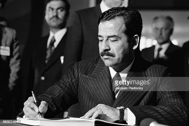 Saddam Hussein signing the visitor's book