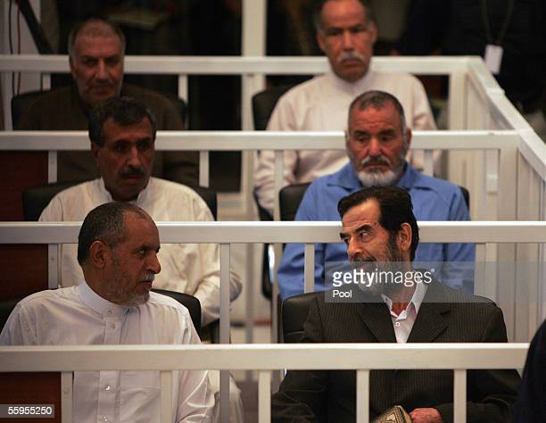 Saddam Hussein speaks to Awad Hamad alBadar as their trial begins begins in Baghdad's heavily fortified Green Zone on October 19 2005 in Baghdad Iraq...