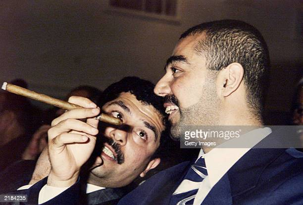 Saddam Hussein's sons Uday Saddam Hussein and his brother Qusay Saddam Hussein attend a meeting of the ruling Ba'th party May 20 2001 in Baghdad...