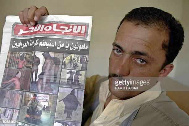 PHOTO Saddam Saleh alRawi holds a newspaper that shows images of US soldiers abusing Iraqi detainees at Abu Ghraib prison at the Iraqi Human Rights...