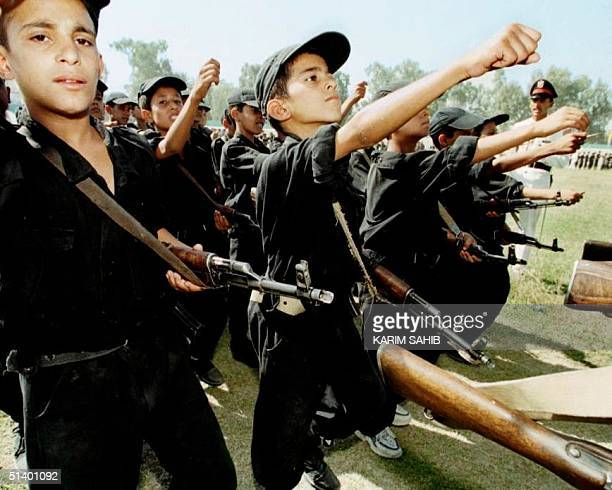 Saddam's cubs named after Iraqi President Saddam Hussein raise their hands during a military march 13 July 1999 at a summer camp in Diala 70 kms...