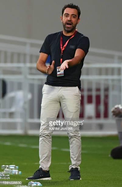 Sadd's coach Xavi Hernandez speaks to his player during the Qatar Cup semi-final football match between Al-Rayyan and Al-Sadd at the Abdullah bin...