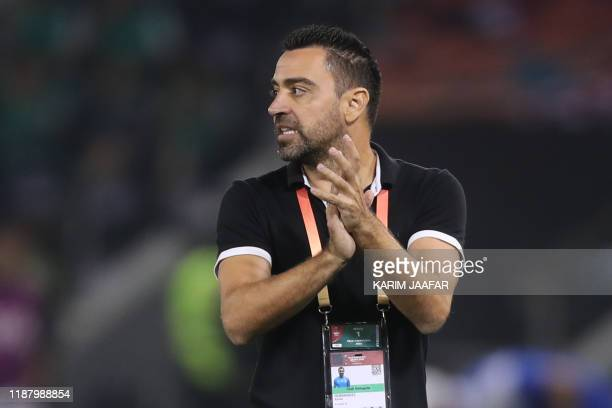 Sadd's coach Xavi speaks to his players during the 2019 FIFA Club World Cup football match between Qatar's Al-Sadd and New Caledonia's Hienghene...