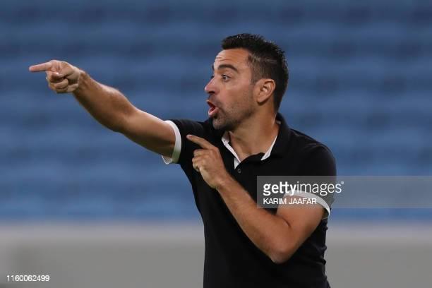 Sadd's coach Xavi speaks to his players during their AFC Champions league play-off football batch between Qatar's al-Duhail and Qatar's al-Sadd at...