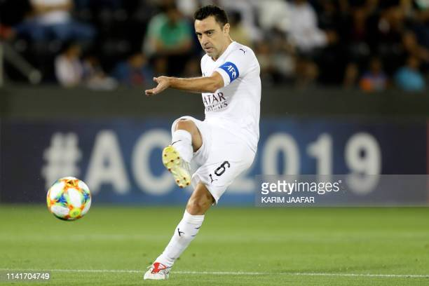 Sadd's midfielder Xavi passes the ball during the AFC Champions League group D football match between Qatar's Al Sadd and Saudi's Al Ahli at the...