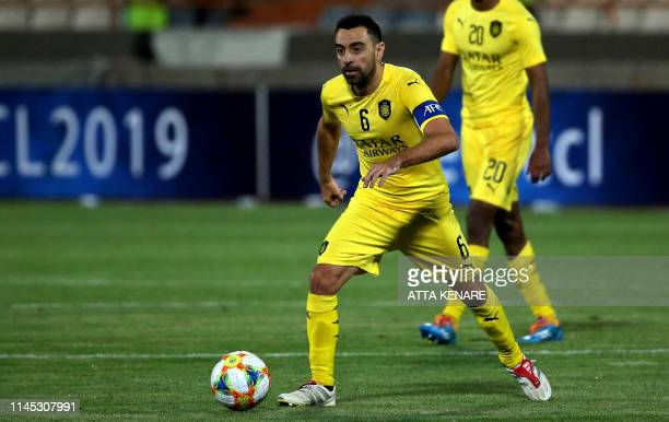 Sadd's midfielder Xavi runs with the ball during the AFC Champions League group D football match between Iran's Persepolis and Qatar's Al Sadd at the...