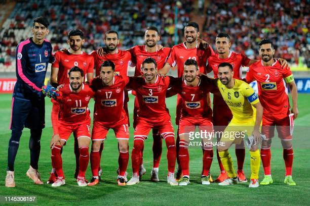 Sadd's Spanish midfielder Xavi poses for a picture with Persepolis' starting eleven during the AFC Champions League group D football match between...