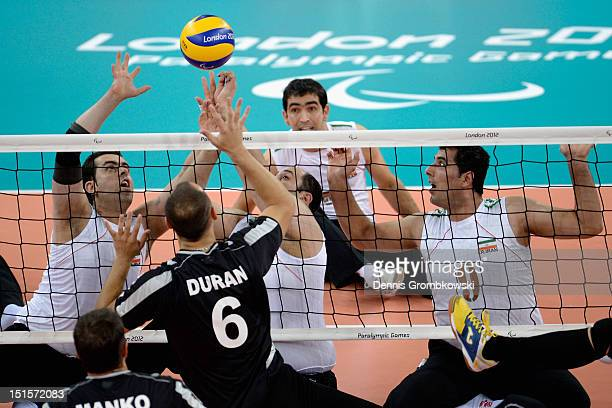 Sadegh Bigdeli of the Islamic Republic of Iran and teammates Davood Alipourian and Seyedsaeid Ebrahimibaladezaei block a ball during the Men's...