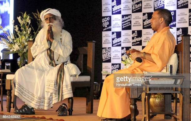Sadhguru the founder of ' Isha foundation' and UP CM Yogi Adityanath having a conversation during the' Rally for Rivers' at BR Ambedkar Auditorium on...